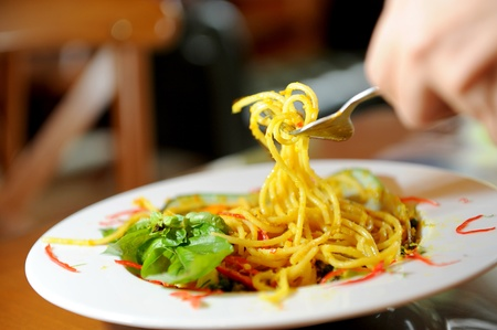 Spaghetti with basil leaves on a fork photo