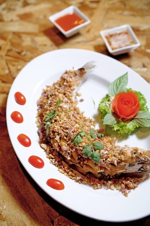 fried fish served with garlic and spices photo