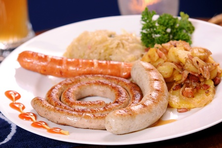 Grilled sausages with potatoes and gravy photo