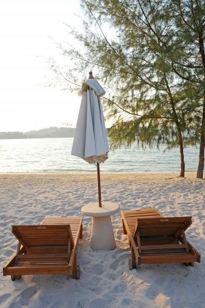 Sunchairs and umbrella on Beach photo