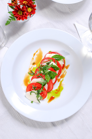 Fresh tomato salad with basil and cheese Stock Photo