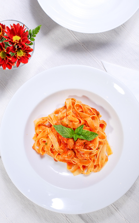 Pasta with basil and tomatoes sauce isolated on white background