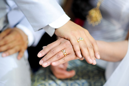 man and woman holding hands with wedding ring