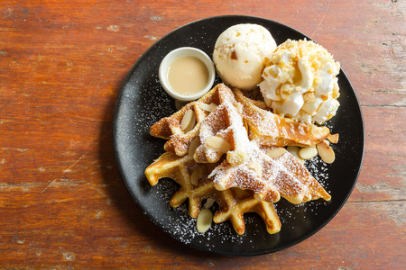 icing sugar: Waffle with rum raisin ice cream and whipping cream on black plate. Decorate with icing sugar and sliced almond. Stock Photo