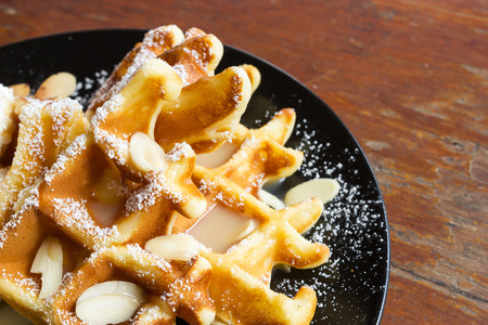 icing sugar: Closeup waffle with caramel topping. Decorate with icing sugar and sliced almond. On black plate over wooden table.