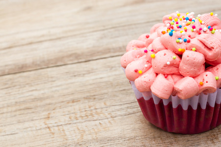 red velvet cupcake: Red velvet cupcake decorated with pink cream and sugar beads on wood background.