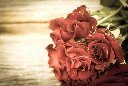 anniversaire: roses rouges Gros plan bouquet sur fond de bois. Vintage style avec vignette sombre.
