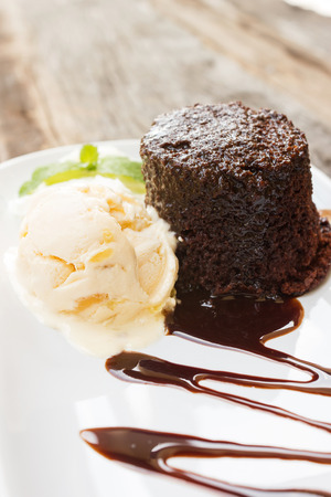 Chocolate cake with rum raisin ice cream and  whipping cream on white plate. Over wooden table. Decorate with chocolate sauce and mint leaf.