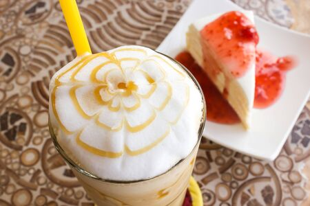 Ice blend caramel coffee with crape cake and strawberry sauce are background. Selecte focus on coffee.