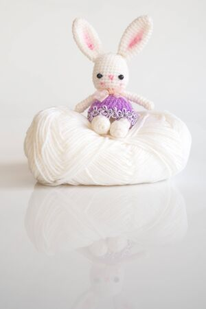 Handmade crochet doll. Cute rabbit doll sitting on white yarn over white background. Amigurumi. Creative and handcraft toy. With copy space. Stock Photo