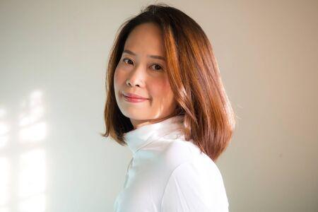 흰 거북이 티셔츠에 통 통한 아시아 여자. 자연의 빛과 테두리 빛 흰색 배경에 초상화. 되돌아가는 행동의 웃음. 스톡 콘텐츠