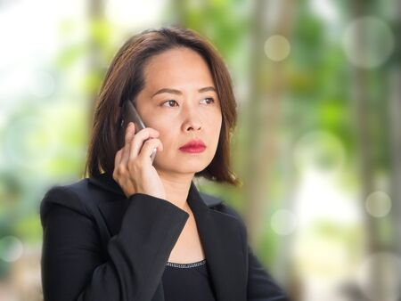Asian woman using smart phone with blur green garden background. Thai business woman were black suit and black vest. Thinking and looking forward emotion. Warm color filter with light bokeh effect. Stock Photo