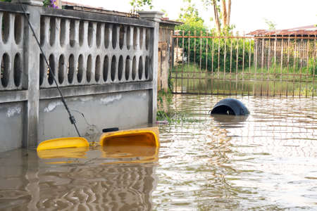 Garbage bin float. Flooding in town. Natural disaster. Environment problem. Banco de Imagens