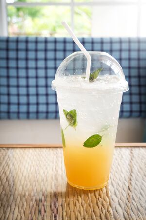 Ice lemon tea with mint and soda. In plastic cup. Refreshment drink. With cafe view and dark vignette.