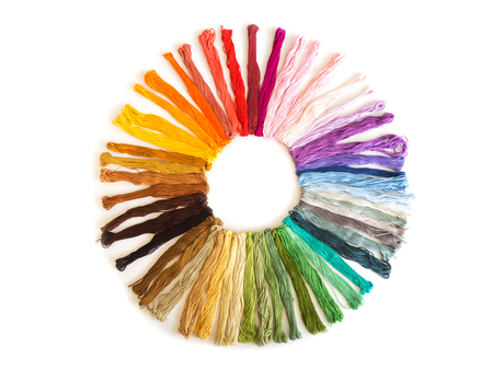 Color cross stitch embroidery on white background. Colorful fabric. Meterial of craft. Favorite hobby. Top view. Sort by color shade in circle shape. Stock Photo