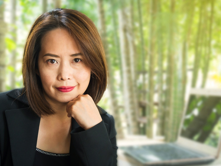 Asian business woman with blur green garden background. Smiling and positive emotion. Confident and looking to camera. Thai business woman were black suit and black singlet. Short hair and black eye with red lip.