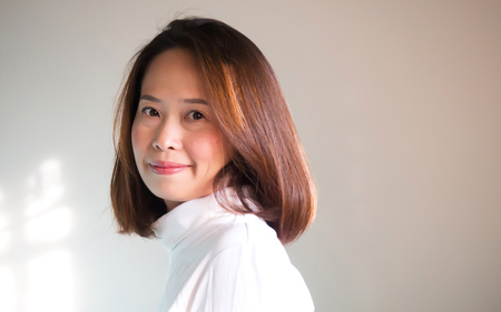 Chubby asian woman in white Turtle Neck T-shirt smiling. Portrait on white background with nature light and rim light. With copy space.