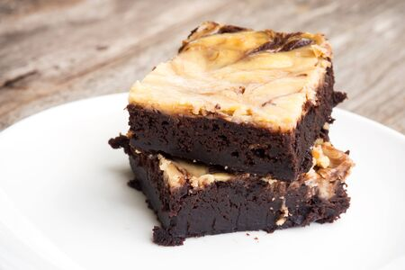 Cheese brownies on white plate. Homemade dessert for chocolate lover. Served on wooden table. Sweet and moist taste. Stock Photo
