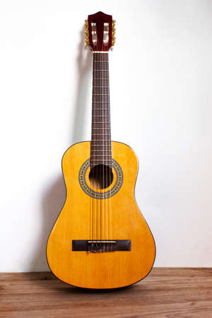 Classic guitar on wood floor with white wall. Favorite string music instrument. Music background.