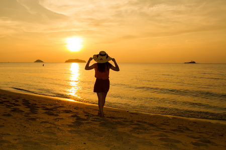 Girl joining sunset on the beach at Koh chang island, Thailand photo
