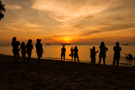 Silhouettes of people enjoying sunset on the  beach at Koh chang island, Thailand photo