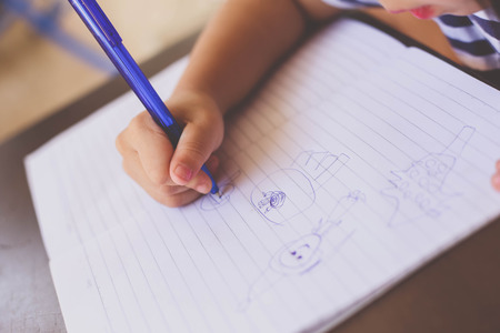 a girl drawing on paper with tablet