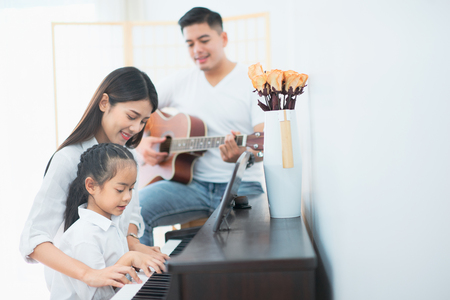 Asian family, Mother and daughter playing piano,Father playing guitar in family band at home, Concept for family relationship Banco de Imagens