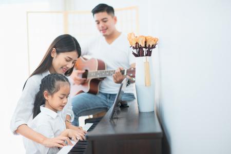Asiatische Familie, Mutter und Tochter spielen Klavier, Vater spielt Gitarre in der Familienband zu Hause, Konzept für Familienbeziehung Standard-Bild