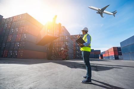 Brygadzista kontroluje ładowanie kontenerów ze statku towarowego na eksport importowy, brygadzista kontroluje przemysłowy kontenerowiec towarowy