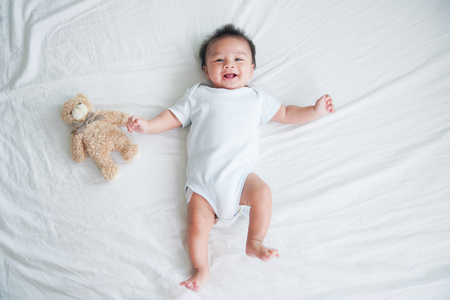 Portrait of a crawling baby on the bed in her room, Adorable baby boy in white sunny bedroom, Newborn child relaxing in bed, Nursery for young children, Textile and bedding for kids Stock Photo