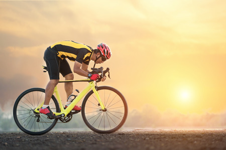 Road bike cyclist man cycling. Biking sports fitness athlete riding bike on an open road to the sunset. Фото со стока