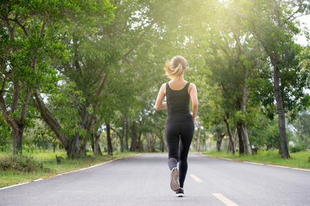 Young fitness sport woman running on the road in the morning, Sun light flare , Selective focus. Stock Photo - 104429978