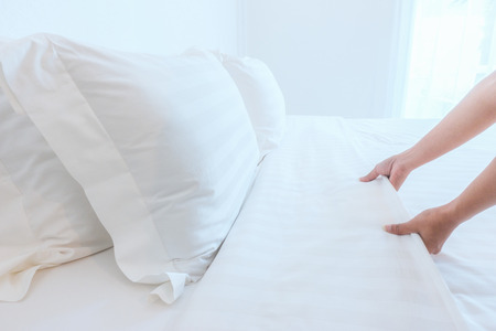 Cerrar mano configurar sábana blanca en la habitación del hotel, enfoque selectivo