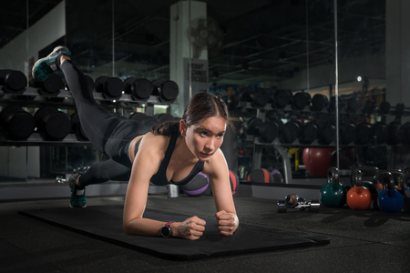 Fit young people doing pushups in a gym looking focused, Gorgeous brunette warming up and doing some push ups a the gym Stock Photo - 110615780