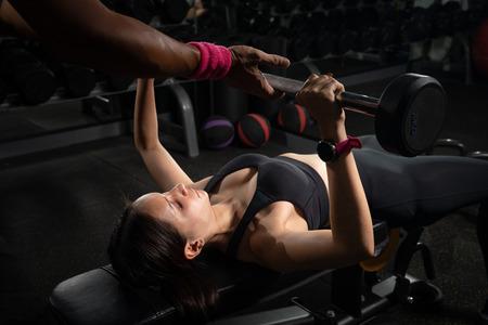 Personal trainer che aiuta la distensione su panca donna in palestra, allenamento con bilanciere Archivio Fotografico