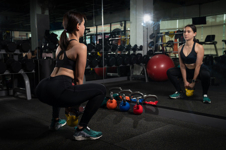 Attractive blonde girl doing exercises with kettle bell. Weightlifting, cross fit and power lifting workout. Sports, fitness concept, Banco de Imagens