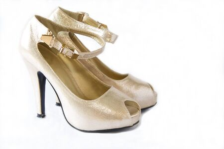 varnished: Pair of gold womens high-heeled shoes isolated on a white Stock Photo