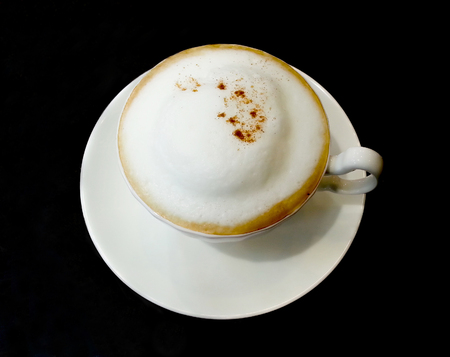 Cappuccino coffee has a bubble in the cup on a black background
