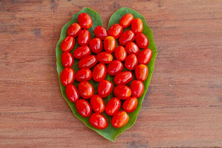 Tomatoes placed on heart shaped leaves