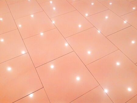 The background is a tile floor with a light shining down below