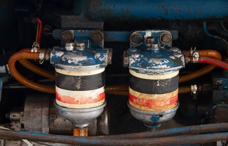 Fuel  oli and hydraulic fluid filters on modern tractor engine, farming machinery maintenance service