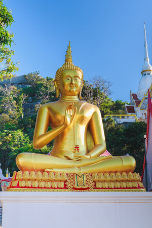The gold buddha statue is sitting outdoor. Stock Photo