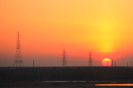 High-voltage tower sunset background photo