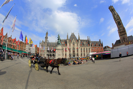 flanders: BRUGES, BELGIUM - 16 APRIL 2015. Horse-drawn carriage with tourists in Grote Markt, Brugge, Flanders in Belgium.