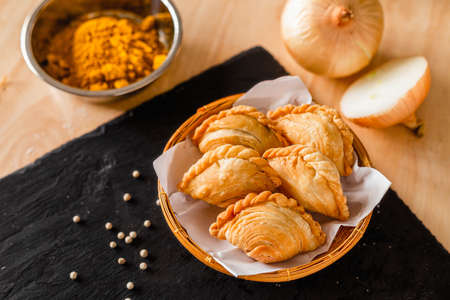 Curry puff on a dark plate and ingredients