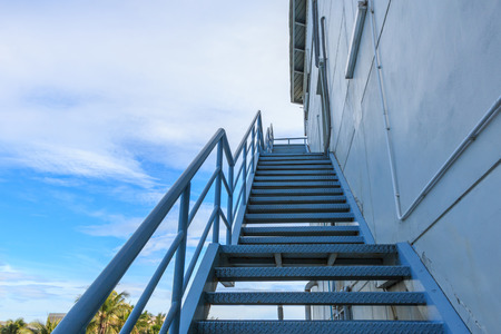 emergency stair: Stairwell fire or emergency exit on wall of building with blue sky background