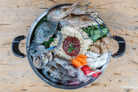 Seafood set of Sukiyaki, Shabu with noodle and vegetable in the pot on wooden table