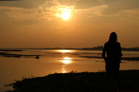 river view: girl standing  on sunset river view