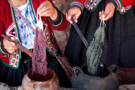 peruvian ethnicity: Demonstration of alpaca wool color dyeing by Peruvian women