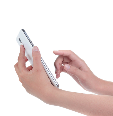Hand holding and operating a smart phone isolated on white Фото со стока